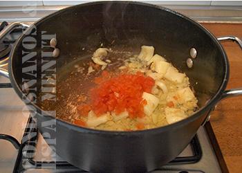 7. Una vez se hayan ablandado la cebolla y el ajo y hayan adquirido un tono dorado, agregar el tomate y desglasar con él el fondo de la cazuela.