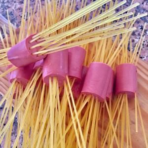2. Clavar los spaguetti en las salchichas.